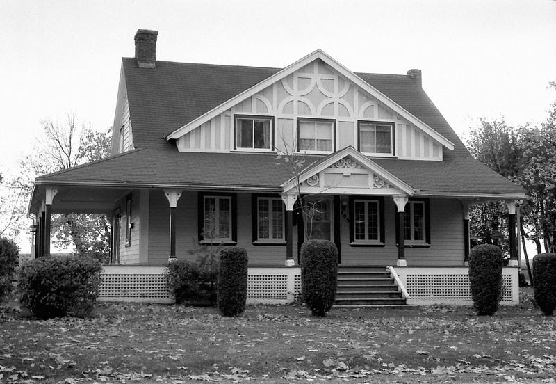 <p>La villa Snetsinger, au sud du chemin, en 1992.<br /><br />Cette maison se singularise par son architecture.&nbsp; Elle a l&rsquo;allure d&rsquo;une demeure&nbsp; traditionnelle, mais on a rehauss&eacute; la fa&ccedil;ade d&rsquo;un grand pignon central perc&eacute; de trois petites fen&ecirc;tres entour&eacute;es d&rsquo;&eacute;l&eacute;ments d&eacute;coratifs d&rsquo;influence n&eacute;o-Tudor.&nbsp; La maison avait &eacute;t&eacute; b&acirc;tie sur le chemin de l&rsquo;&eacute;glise, en 1854, par Pierre Gosselin, un menuisier de Cacouna.&nbsp; Ce dernier avait &eacute;t&eacute; embauch&eacute; par l&rsquo;architecte-sculpteur Fran&ccedil;ois-Xavier Berlinguet qui travaillait &agrave; la d&eacute;coration int&eacute;rieure de l&rsquo;&eacute;glise.&nbsp; En 1861, F&eacute;lix F. Gagnon, jeune agriculteur qui venait de se marier, l&rsquo;acheta et la fit d&eacute;m&eacute;nager sur cette terre agricole.&nbsp; Il la loua &agrave; des touristes pendant plusieurs ann&eacute;es avant de la vendre &agrave; John Gray Goodal Snetsinger, marchand g&eacute;n&eacute;ral de Cornwall (Ontario), en 1876.&nbsp; Monsieur Snetsinger fut &agrave; la fois d&eacute;put&eacute; au parlement ontarien (de 1871 &agrave; 1879) et maire de Cornwall, puis il fut &eacute;lu d&eacute;put&eacute; &agrave; Ottawa o&ugrave; il si&eacute;gea pendant quatre ans.&nbsp; Il transforma la maison de fa&ccedil;on si agr&eacute;able que sa famille l&rsquo;occupa pendant pr&egrave;s de 100 ans.<br /><br />Source photo:<br />Photo : Lynda Dionne</p>