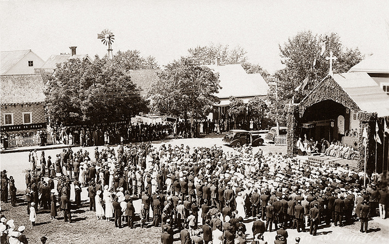 <p>The 1937 Eucharistic Congress in front of the parish hall.<br /><br />This rectangular building with a hipped roof and broken gable was built in 1932 to replace the small &laquo; public hall &raquo; near the cemetery.<br /><br />The current parish hall was inaugurated during the agricultural fair on March 23 and 24, 1933 and, after being blessed by Right Reverend Georges Courchesne, the Bishop of Rimouski, the Enfants de Marie put on a play in front of a large crowd.<br /><br />Photo source :<br />Mus&eacute;e du Bas-Saint-Laurent, Belle-Lavoie Collection</p>