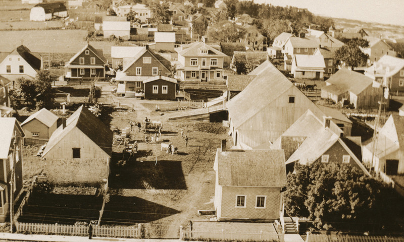 <p>A view of the village from the church belfry.&nbsp; We can see the farmer&rsquo;s wagons loaded with milk cans driving down Robichaud Street around 1930.<br /><br />From 1913 to 1940, the Rue de la Beurrerie was bustling with activity. Cacouna&rsquo;s farmers frequented &ldquo;Creamery Street,&rdquo; their horse-drawn carts laden with milk cans. At the creamery, buttermaker Louis L&eacute;vesque weighed the milk and cream and determined the fat content. A steam engine powered the creamery&rsquo;s big churn, producing substantial amounts of butter, especially in July and August. Fifty-pound boxes of butter were stored in the ice house and distributed to shopkeepers in Cacouna and the surrounding area.<br /><br />Photo source:<br />Photo : Aim&eacute; Rivard, Normand Rivard Collection</p>