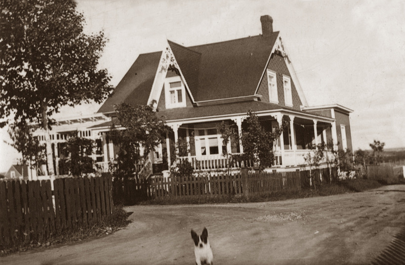 <p>House and store of the Louis Boss&eacute; family around 1940.<br /><br />Near L&eacute;vesque&rsquo;s creamery, on the corner of Robichaud and Mgr Landry streets, Jos Moreault had a store selling food staples and hardware. Louis Boss&eacute; and his wife Alice Dionne bought the store in 1930. For the next ten years, farmers, clients of the creamery and families from the neighbourhood shopped there, piling milk cans, jugs of vinegar and molasses, bags of flour and sugar, boxes of nails, screws and putty, pots and pans and garden tools into their cars.<br /><br />Boss&eacute; was also a horsetrader, buying horses in western Canada and shipping them through Montreal where they were loaded onto trains. He sometimes received two train cars full of horses at the Cacouna train station. Boss&eacute; would herd them down Rue de l&rsquo;&Eacute;glise, through the village and onto a pasture south of his stable behind the L&eacute;vesque creamery.<br /><br />Photo source :<br />Ghislaine Boss&eacute; Collection</p>