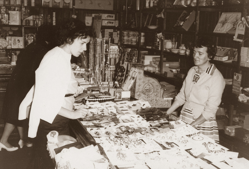 <p>In the five-and-dime store, Th&eacute;r&egrave;se, daughter of Antonio Sirois, answering her clients in 1961.<br /><br />The old general store was replaced in turn by a five-and-ten souvenir and handicrafts shop. To this date, the community elders can still bear witness to the days when the Post Office occupied part of the Antonio Sirois general store (1928-1958) and wistfully recall how kindly his daughters, May, Yolande and Th&eacute;r&egrave;se welcomed them.<br /><br />Photo source :<br />Antonio Sirois Family Collection</p>