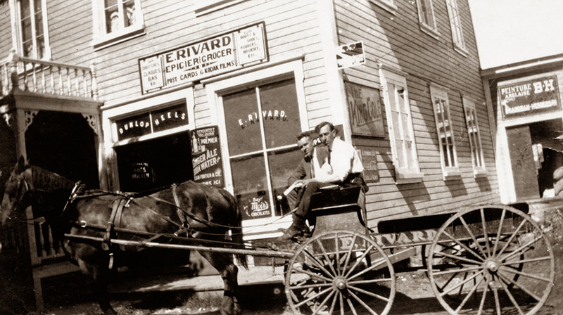 <p>The assistant shopkeepers Paul-&Eacute;mile and Aim&eacute; Rivard, seated in the delivery wagon of their father Eus&egrave;be&rsquo;s general store, circa 1920.<br /><br />At shoemaker Eus&egrave;be Rivard&rsquo;s shop, local families and visitors could buy not only shoes, but also everyday products and food staples. Dry goods like flour and sugar in 100-pound sacs arrived regularly at the Cacouna wharf by schooner and were delivered to the warehouse behind the store. Local residents and summer visitors were among Rivard&rsquo;s many customers.<br /><br />Photo source :<br />Normand Rivard Collection</p>