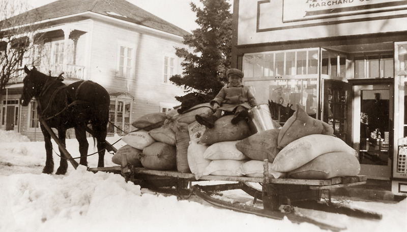 <p>Young Marc, son of Aim&eacute;, seated on a load of sacks ready for delivery, around 1935.<br /><br />Starting in 1930, he began making home deliveries to build up his customer base. He rented a horse from his neighbour, L&eacute;o Vaillancourt, hitched up his delivery cart and drove out to the second concession road. On each trip, he piled his cart high with large sacks of Lac des Bois bread flour, 100-pound bags of sugar, 85-gallon casks of maple syrup or vinegar, and 140-pound bags of salt for the fishermen. On his door-to-door rounds, he also provided farmers with animal feed such as bags of oats, bran, &ldquo;brown shorts&rdquo; and wheat middlings.<br /><br />Photo source :<br />Normand Rivard Collection</p>