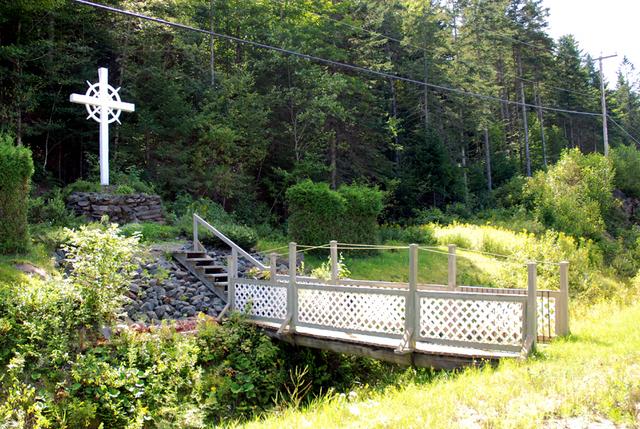 <p>Cette croix de chemin est mise en valeur, puisqu&#39;elle est install&eacute;e sur un monticule de pierre avec anneaux concentriques et angles chanfrein&eacute;s, accessible par l&#39;entremise d&#39;une passerelle de bois.</p>