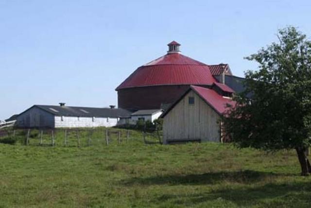 <p>Construite en 1907, cette grange ronde situ&eacute;e sur la ferme de la famille Holmes est une des derni&egrave;res de la r&eacute;gion. Reconnue officiellement comme site historique, elle est ouverte au public. Selon des croyances populaire,&nbsp; les premiers b&acirc;tisseurs de granges circulaires &eacute;taient persuad&eacute;s qu&rsquo;en raison de l&rsquo;architecture de ces granges, le diable ne pouvait se cacher dans les coins! Les Shakers faisaient partie d&rsquo;une secte religieuse annon&ccedil;ant la fin du monde pour bient&ocirc;t, comme quoi ce genre de sc&eacute;nario apocalyptique ne date pas d&#39;hier...<br />Pour plus de d&eacute;tails: townshipsheritage.com/node/2100<br />&nbsp;</p>