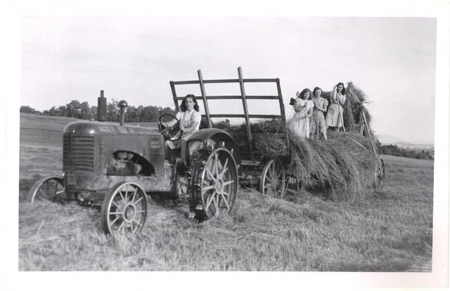 <p>Jeunes filles faisant les foins avec une chargeuse, vers 1945.&nbsp; Le tracteur &agrave; roues de fer est conduit par Claire Lavoie. Sur la charrette de gauche &agrave; droite : H&eacute;l&egrave;ne B&eacute;langer, une amie de Th&eacute;r&egrave;se Lavoie, Jeanne d&rsquo;Arc et Th&eacute;r&egrave;se.</p>