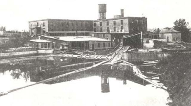 <p>La George Gale &amp; Sons Factory, en bordure de la rivi&egrave;re Coaticook, avec son ch&acirc;teau d&rsquo;eau qui culmine derri&egrave;re, un vestige toujours existant de nos jours (&agrave; l&#39;emplacement de la st&egrave;le de M. Gale).</p>