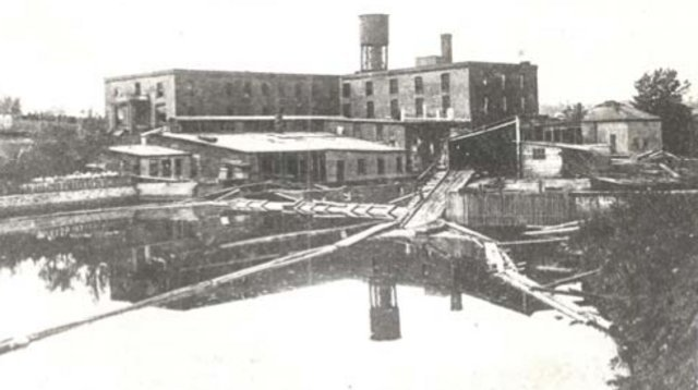 <p>View of the George Gale &amp; Sons factory on the banks of the Coaticook River with the water tower rising up behind it. The water tower remains today a vestige of the past (with its monument to Mr. Gales beside It)</p>