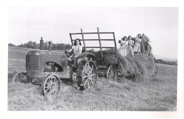 <p>Young girls haying with a loader in 1945. The steel-wheeled tractor is driven by Claire Lavoie. On the cart, from left to right: H&eacute;l&egrave;ne B&eacute;langer, a friend of Th&eacute;r&egrave;se Lavoie, Jeanne d&#39;Arc, and Th&eacute;r&egrave;se.</p>