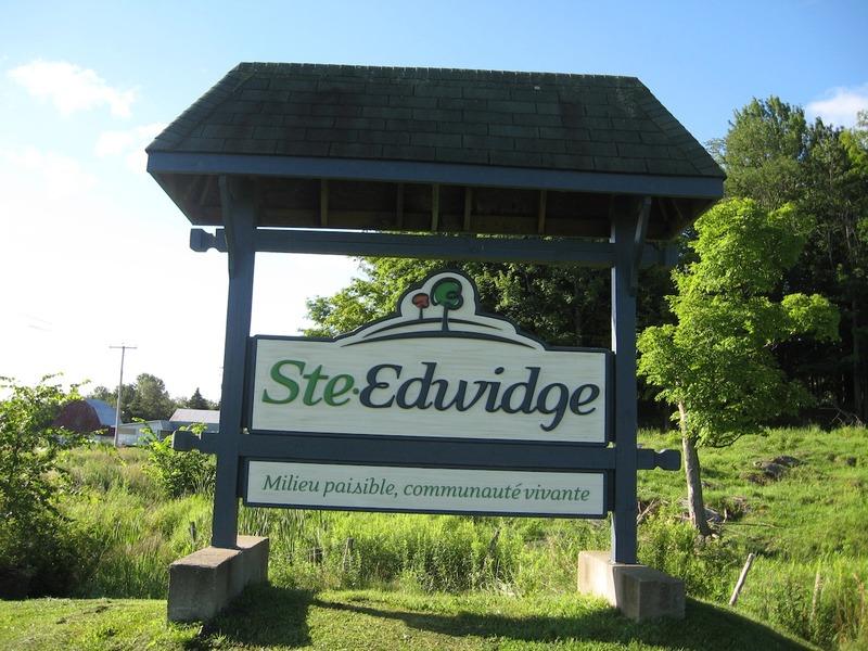 <p>Ce panneau marque l&#39;entr&eacute;e de Sainte-Edwidge-de-Clifton. Il pr&eacute;sente aussi la devise de la municipalit&eacute;.&nbsp;Ce sont des familles canadiennes-fran&ccedil;aises qui sanctionnent en 1865 la paroisse et en 1895 la municipalit&eacute; du canton de Sainte-Edwidge-de-Clifton, sous la protection de la tr&egrave;s pieuse duchesse de Sil&eacute;sie, Hedwidge, qui a v&eacute;cu de 1174 &agrave; 1243.</p>