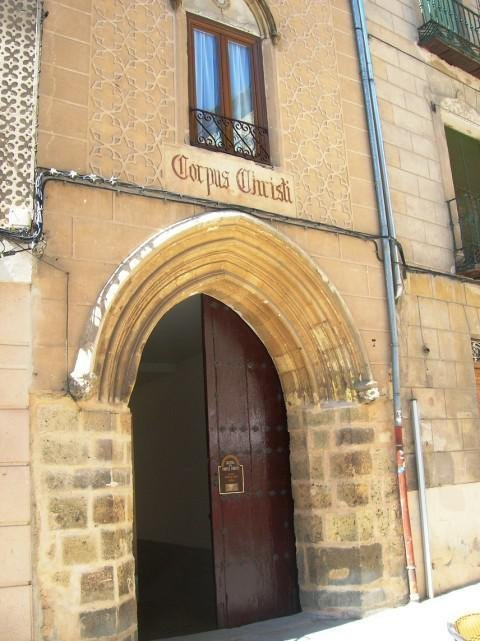 <p>The gateway to Corpus Christi Church is located on Real st. A gothic arch of the XV century allows to enter a patio, to the end of which a door with a horseshoe can be found. In the central part of it, you can see the inscription: &quot;Soli Deo honor et gloria&quot; (Glory to God alone) and in an angle, the date of the first restoration.<br /><br />There is a legend saying that in 1410 the sacristan of the San Facundo Church was in a lot of debt and asked for a loan to a rich Jewish doctor from the city. He accepted on condition that he received in exchange a consecrated Host. The sacristan agreed and the exchange happened one night un a street now called &quot;Malconsejo&quot; (bad advice), to remember this event. The doctor and other Jews got together in the Great Synagogue of Segovia and they decided to throw the consecrated Host in a saucepan of boiling water. But before it brushed the water, the host stayed suspended in the air. Then the synagogue started shaking and a crack opened in a wall where the body of Christ miraculously got out, who crossed the city flying to take refuge in the Monastery of the Holy Cross.<br /><br />When the bishop of Segovia learned about it, he wanted to know how it happened and conducted an investigation. The sacristan immediatly confessed and the doctor was arrested and sentenced to death. The King Juan II confiscated the synagogue and offered to the bishop who dedicated it to Christian worship and had it named the Corpus Christi Church, as an account of what happened there. He let the religious community of the Clares who still occupies it.<br />At the entrance of the Corpus Christi Church, a painting of Vincente Cutanda who has the title &quot;The Eucharistic Miracle&quot; illustrates this event.<br /><br />This church is regarded as a sacred place for the Christian and Jewish religions. It was used as a synagogue until 1410, date upon which it was taken from the Jewish community. Among the five synagogues in the city, this 