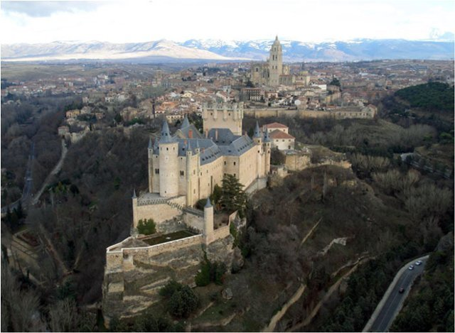 <p>The Alcazar of Segovia is one of the most remarkable castles of Spain. It only takes a little imagination to turn it into a legendary place.<br /><br />The fortress, whose silhouette resembles a ship, enjoys a privileged situation, at the tip of a rocky spur, at the foot of which the Eresma and Clamores rivers meet.<br /><br />Probably inhabited since the Celtic times, the fortress was turned into Alcazar (royal residence) at the XIII century and acquired its gothic appearance at the time of Juan I and Enrique IV. Its restoration was continuous after a major fire that happened in 1862 and that was on the verge of destroying it completely. However, in 1882, during the reign of Alfonso XII, its reconstruction began and has never been abandoned ever since.</p>