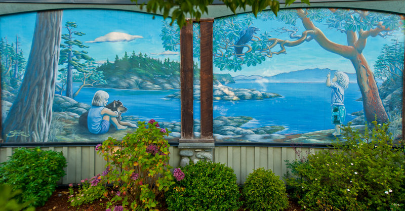 LOCATION: 5500 Wharf Ave (exterior of Sechelt Animal Hospital)<br />MURAL:<em> Life on the Coast</em>, 2004<br />ARTIST: Dean Schutz<br />MEDIUM: Acrylic and latex paints<p>These two murals were commissioned by the Sechelt Animal Hospital and painted by local artist and muralist Dean Schutz. On the panels facing Wharf Ave. you will see two young children enjoying &ldquo;Life on the Coast&rdquo; amongst the trees and wildlife. The young girl is the artist&rsquo;s daughter Zoey with her dog Java. Standing nearby and having a chat with a raven is the artist&rsquo;s son Cole.</p>