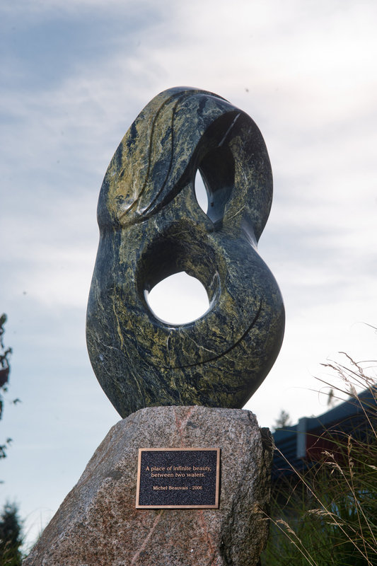 <p>LOCATION: Municipal Hall Sculpture Garden, Rosina Giles Way<br />SCULPTURE: <em>A Place of Infinite Beauty, Between Two Waters</em>, 2006<br />ARTIST: Michel Beauvais<br />MEDIUM: Serpentine stone and granite<br /><br />This sculpture was the inaugural artwork for the Sechelt Municipal Hall Sculpture Garden. Artist Michel Beauvais&rsquo; proposal was chosen from a number of applications submitted by local artists. When considering this project, Beauvais reflected on what &ldquo;Sechelt&rdquo; meant to him, and he kept coming back to the idea of water &ndash; its feel and its energy. From here he developed the concept of Sechelt as a place of &ldquo;infinite (&infin;) beauty&rdquo; located between two waters. The basic form of the sculpture looks like an infinity symbol turned on its side, and allows both light and wind to flow through the piece. The wavy lines carved into the top of the sculpture are meant to mimic crashing ocean waves.</p>