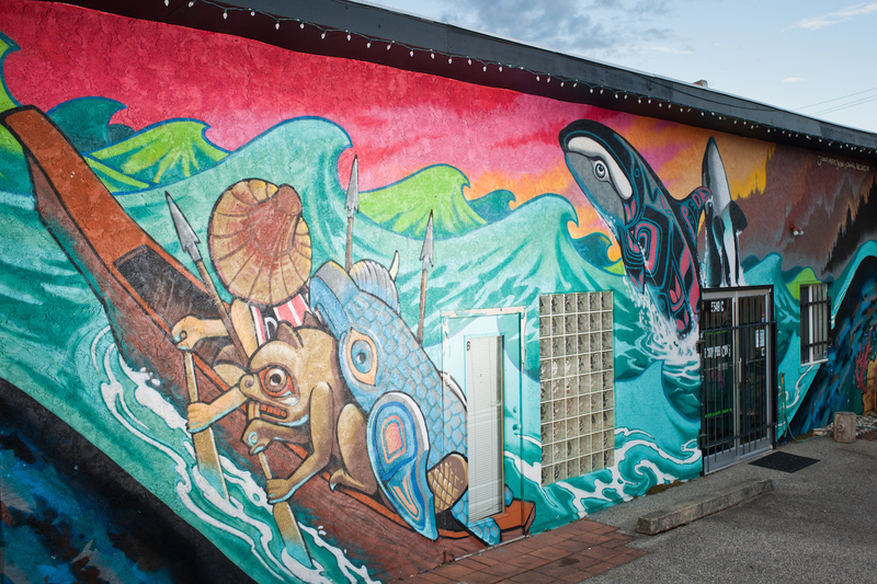 <p>The section of the mural closest to the Custom Tattoo shop&rsquo;s entrance is more heavily influenced by the style of Severino &ldquo;DOING&rdquo; Estevez. A professional tattoo artist originally from Barcellona, Spain, Estevez owns and operates the store Doing Tattoo in Edmonton, Alberta. On the left side of the painting two weathered boats, one with a pirate flag, coast though dark waters as sharks circle their hulls. Brightly coloured jellyfish sweep across the centre of the painting and look as though they are caught up in a whirlpool of waves, salmon and coral. At the right side of the painting is a tribute to the famous <em>Spirit of Haida Gwaii</em> (1986) sculpture by the late Bill Reid.</p>
