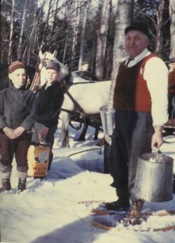 <p>Isidore en raquettes en train de ramasser l&rsquo;eau d&rsquo;&eacute;rable avec ses petits-enfants vers 1950</p>