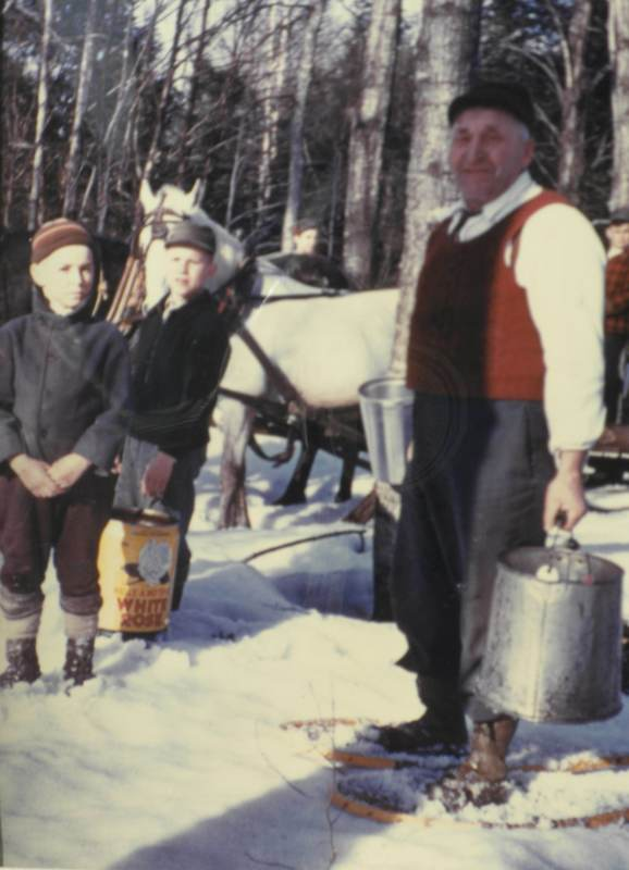 <p>Isidore on snowshoes gathering sap with his grandchildren, circa 1950.</p>