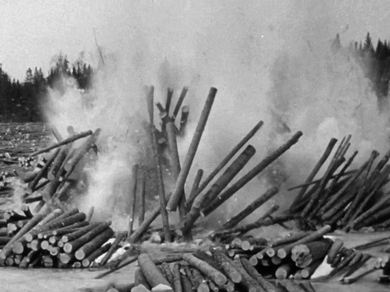 <p>Photographie d&rsquo;une explosion d&rsquo;un emb&acirc;cle sur la rivi&egrave;re Kiamika, 1956, tir&eacute;e du film La&nbsp; drave de l&#39;ONF.<br /><br />Quand un emb&acirc;cle survenait, le contrema&icirc;tre d&eacute;l&eacute;guait une &eacute;quipe de draveurs afin de le briser le plus rapidement. Il s&rsquo;agissait d&rsquo;aller, au milieu du courant, couper &agrave; coups de hache ou d&eacute;bloquer avec le peavy, la pi&egrave;ce qui servait de clef &agrave; l&rsquo;emb&acirc;cle. Au moment o&ugrave; la pi&egrave;ce commen&ccedil;ait &agrave; c&eacute;der, le draveur courait sur les billots &agrave; rebours du courant pour regagner le rivage. Lorsqu&rsquo;il &eacute;tait vraiment impossible de d&eacute;faire l&rsquo;emb&acirc;cle, le contrema&icirc;tre recourait &agrave; la dynamite. Il d&eacute;signait un draveur pour aller placer un ou plusieurs b&acirc;tons de dynamite &agrave; l&rsquo;endroit pr&eacute;cis o&ugrave; l&rsquo;emb&acirc;cle semblait se produire. Le draveur allumait les b&acirc;tons de dynamite et revenait en courant et en sautant sur les billots. En m&ecirc;me temps que le dynamitage, on tentait de hausser le niveau de l&rsquo;eau par l&rsquo;ouverture d&rsquo;une digue en amont.&nbsp;</p>