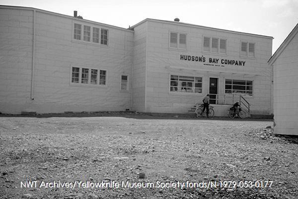 <p>Cet immeuble a &eacute;t&eacute; b&acirc;ti par Compagnie de la Baie d&rsquo;Hudson en 1945 pour remplacer un magasin, plus petit, d&eacute;truit par un incendie. On venait y acheter les produits exclusifs de la Baie dont la fameuse couverture &agrave; rayures. A partir de 1960, l&rsquo;&eacute;difice qui se dresse devant vous a servi exclusivement d&rsquo;entrep&ocirc;t.<br /><br />Source photo: NWT Archives/Yellowknife Museum Society fonds/N-1979-053-0177.</p>