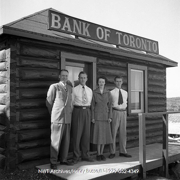 <p>Cette cabane rustique&nbsp; a, de 1944 &agrave; 1951, abrit&eacute; une succursale de la banque Toronto Dominion.&nbsp;Elle fut construite par John Stakson en 1939 sur la rue principale du vieux Yellowknife, pr&egrave;s de The Rock, alors l&rsquo;art&egrave;re commerciale principale de la ville. La photo date de 1950.<br /><br />Source photo: NWT Archives/Henry Busse/N-1979-052-4349.&nbsp;</p>