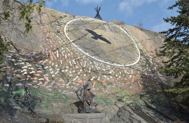 <p>This sculpture, set up at the foot of McAvoy Rock, displays a Dene drum, a symbol of both the sun and the circle of life. It is made from a block of bronze. Initially it was made from a block of marble formed on the shore of Great Slave Lake.&nbsp;<br /><br />The drum and music signify the universality of language.&nbsp;This music becomes water and waves, and illustrates three elements:<br /><br />- The lakes and rivers, home to the fish, the mascot animal of the M&eacute;tis;<br />- Earth, as represented by the bear, the mascot to the Inuvialuit;<br />- Air, represented by the eagle, the mascot of the Dene.<br /><br />The face of McAvoy Rock also displays a crow with outspread wings. The crow is a mythical figure of the North.</p>