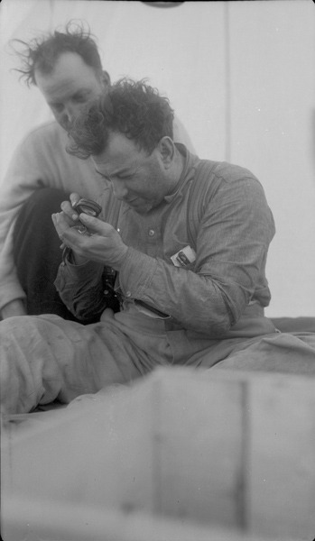 <p>Harry Weaver (holding the magnifying glass) and Sam Otto, one of Yellowknife&#39;s pioneers.<br /><br />Photo source: NWT ArchivesSam Otto fondsN-2002-002 0019.</p>
