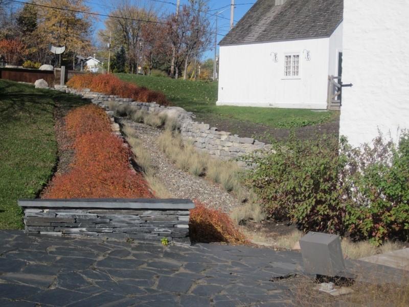 <p>&copy; Moulin des J&eacute;suites de Charlesbourg<br /><br />L&rsquo;imposant barrage qui domine la partie sup&eacute;rieure du terrain en pente est une reconstitution et d&eacute;montre l&rsquo;importance de la retenue d&rsquo;eau n&eacute;cessaire &agrave; la mise en marche de la grande roue qui lan&ccedil;ait les engrenages et faisait tourner les composantes de la moulange.&nbsp;<br />Sur le ponceau qui traverse le barrage, un impressionnant canal d&rsquo;amen&eacute;e d&rsquo;eau, fait de pierres calcaires, descend jusqu&rsquo;&agrave; la grande roue. Un canal d&rsquo;&eacute;vitement permet de d&eacute;tourner l&rsquo;eau lorsque le meunier n&rsquo;utilise pas les m&eacute;canismes de meunerie.</p>
